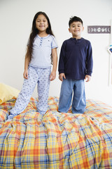 Brother and sister standing on bed together