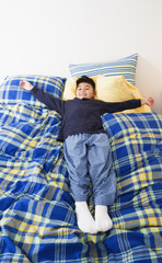 Boy lying down on top of bed