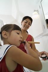 Daughter using makeup brush