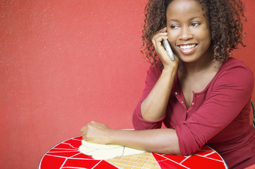 Woman using mobile phone at outdoor table