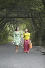 Two women walking on a road