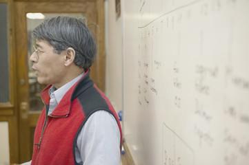 Profile of male teacher at whiteboard