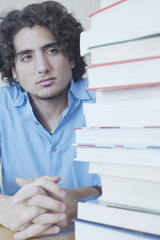 Teenage boy looking at stack of books