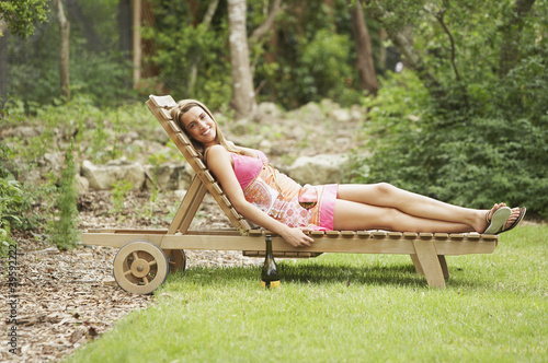 Portrait of woman lying on lounge chair
