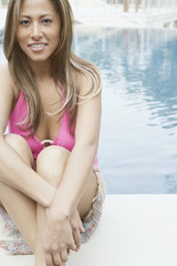 Young woman sitting at poolside