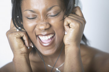 African American woman singing and wearing headphones