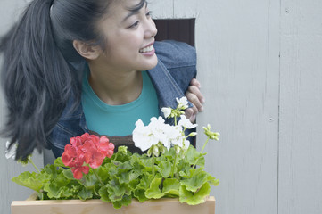 Asian woman leaning out window with flowerbox