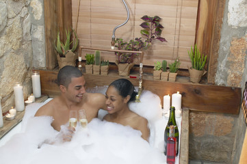 African American couple in bubble bath with champagne