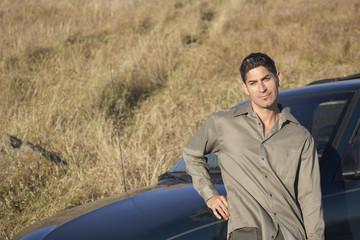 Portrait of man beside his car