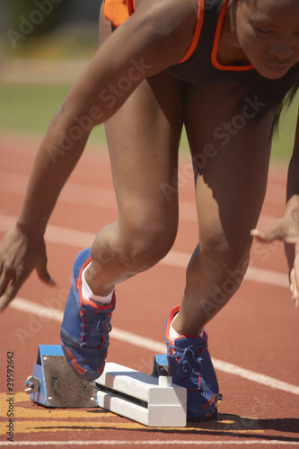 Female runner leaving starting blocks