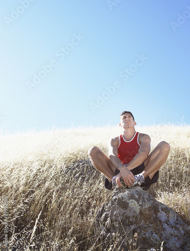 Man resting on hillside rock