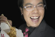 Asian businessman with eyeglasses eating take out food