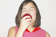 Studio shot of Asian woman eating apple