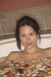 Woman in bathtub filled with water and flower petals