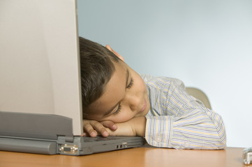 Young boy asleep on laptop computer