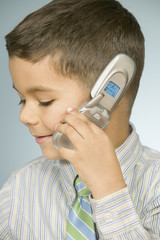 Close up of young boy talking on mobile phone
