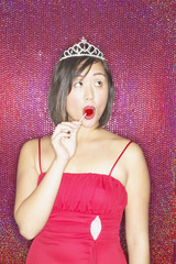 Asian woman wearing evening dress and tiara and eating lollipop