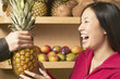 Asian woman holding pineapple in grocery store