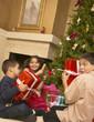 Hispanic siblings shaking Christmas gifts