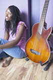 African American woman sitting next to guitar