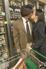 Asian couple kissing in grocery store