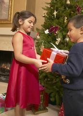 Young Hispanic girl giving brother Christmas gift