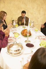 Hispanic family saying grace at dinner table