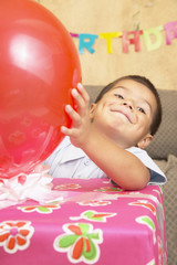 Young Hispanic boy with large gift and balloon