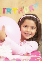 Young Hispanic girl with large gift and balloon
