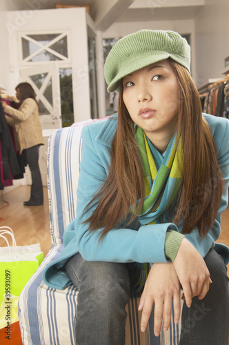 Asian woman sitting on chair in boutique