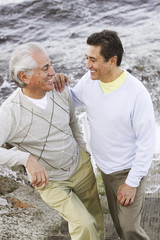 Hispanic father and adult son smiling at each other