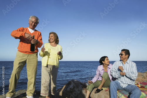 Extended family celebrate on rocky shore