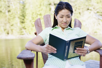 Woman sitting on deck by lake reading
