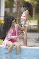 Mother applying lotion to daughter's leg at side of pool