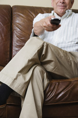 Mid section of elderly man sitting on couch with remote control in hand