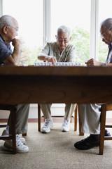 Three elderly men sitting at table playing game