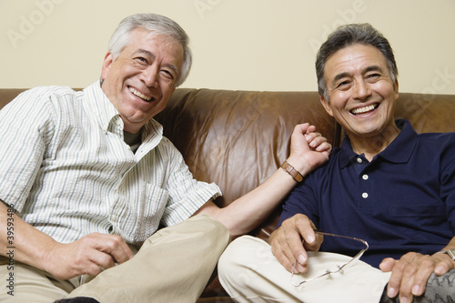 Portrait of elderly men sitting on the couch laughing