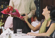 Waiter handing woman flowers at restaurant