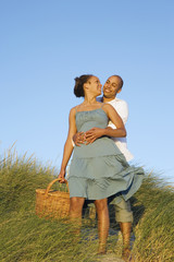 Couple hugging with picnic basket at beach
