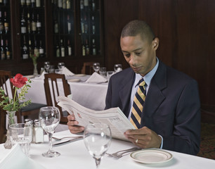 Businessman reading newspaper at restaurant
