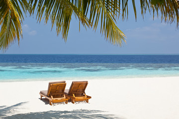 Two sun loungers on a deserted beach