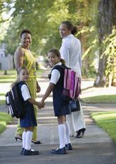 Rear view of women and girls walking down sidewalk