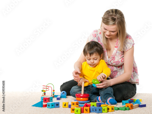 Mother and son on the carpet with toys
