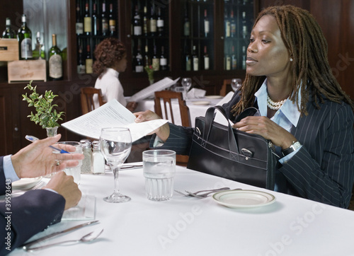 Businesswoman handing papers to man in restaurant