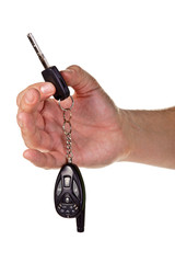Hand holding car keys and a remote control