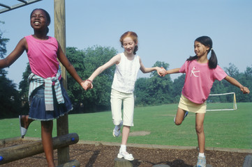 Three girls playing in park while holding hands