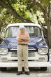 Portrait of elderly man standing in front of old pickup truck