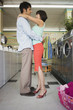 Couple hugging at laundromat