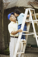 Little girl giving grandpa a kiss while standing on a ladder