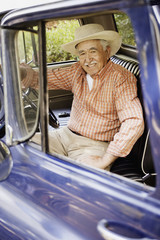 Portrait of elderly man sitting in old pickup truck